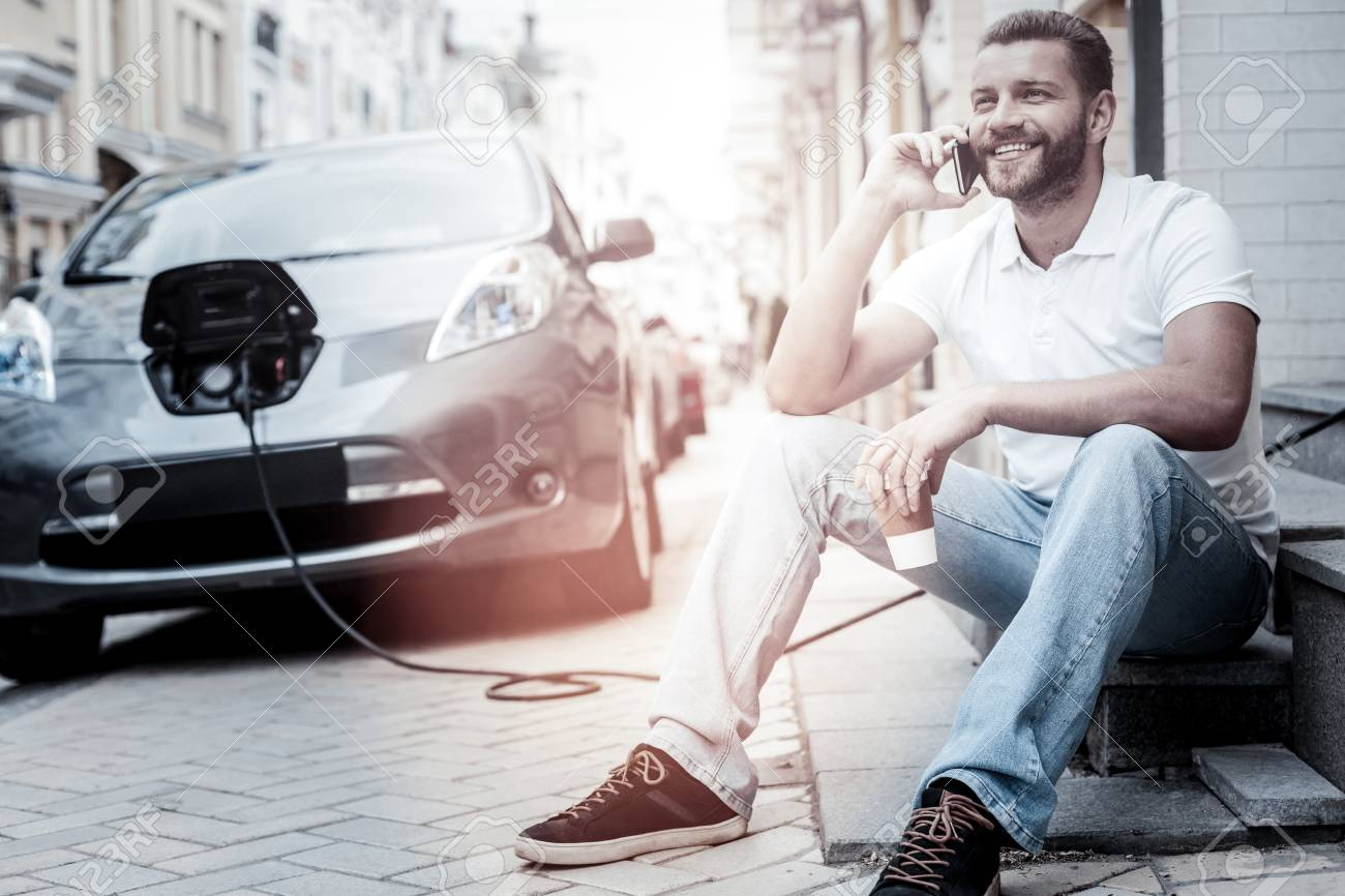 Hello its me. Positive minded millennial guy beaming while drinking coffee and listening to his friend talking on phone with his modern electric car charging in the background. - 94649357