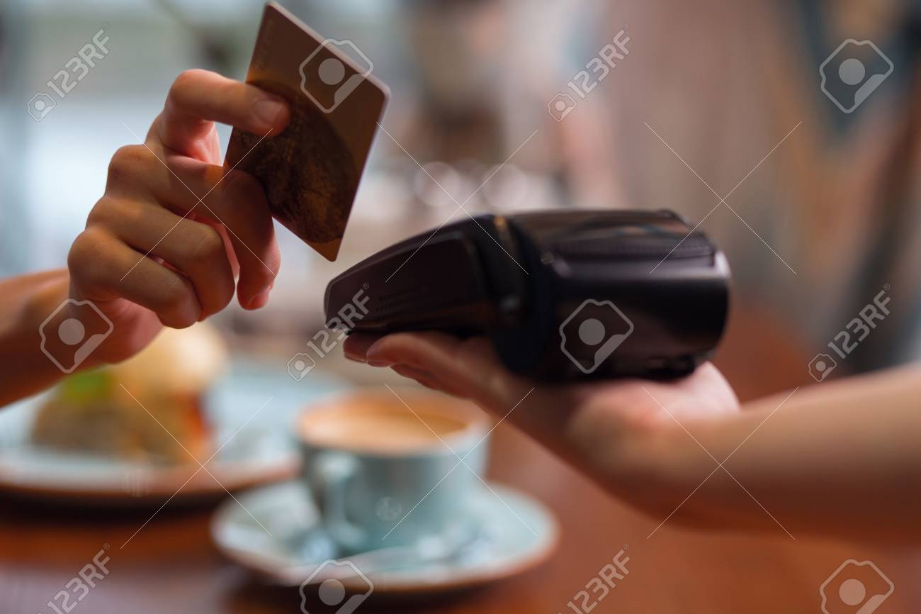 Credit card usage. Moment of payment with a credit card hold by female hand through terminal which carried by another hand - 95653010