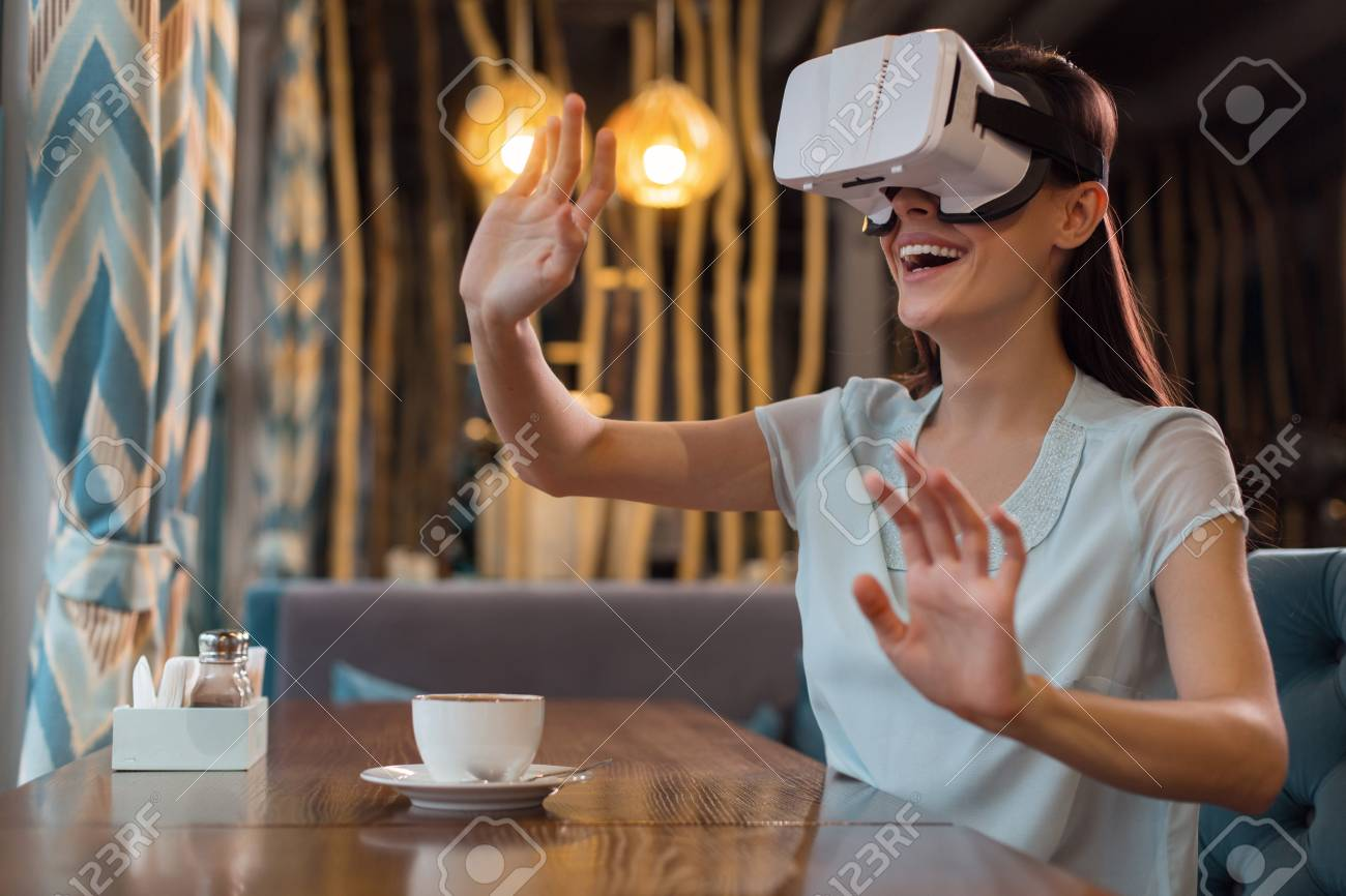 fdc813ca0c9 Impressive VR. Cheerful creative happy woman moving hands while shouting  and wearing VR glasses Stock