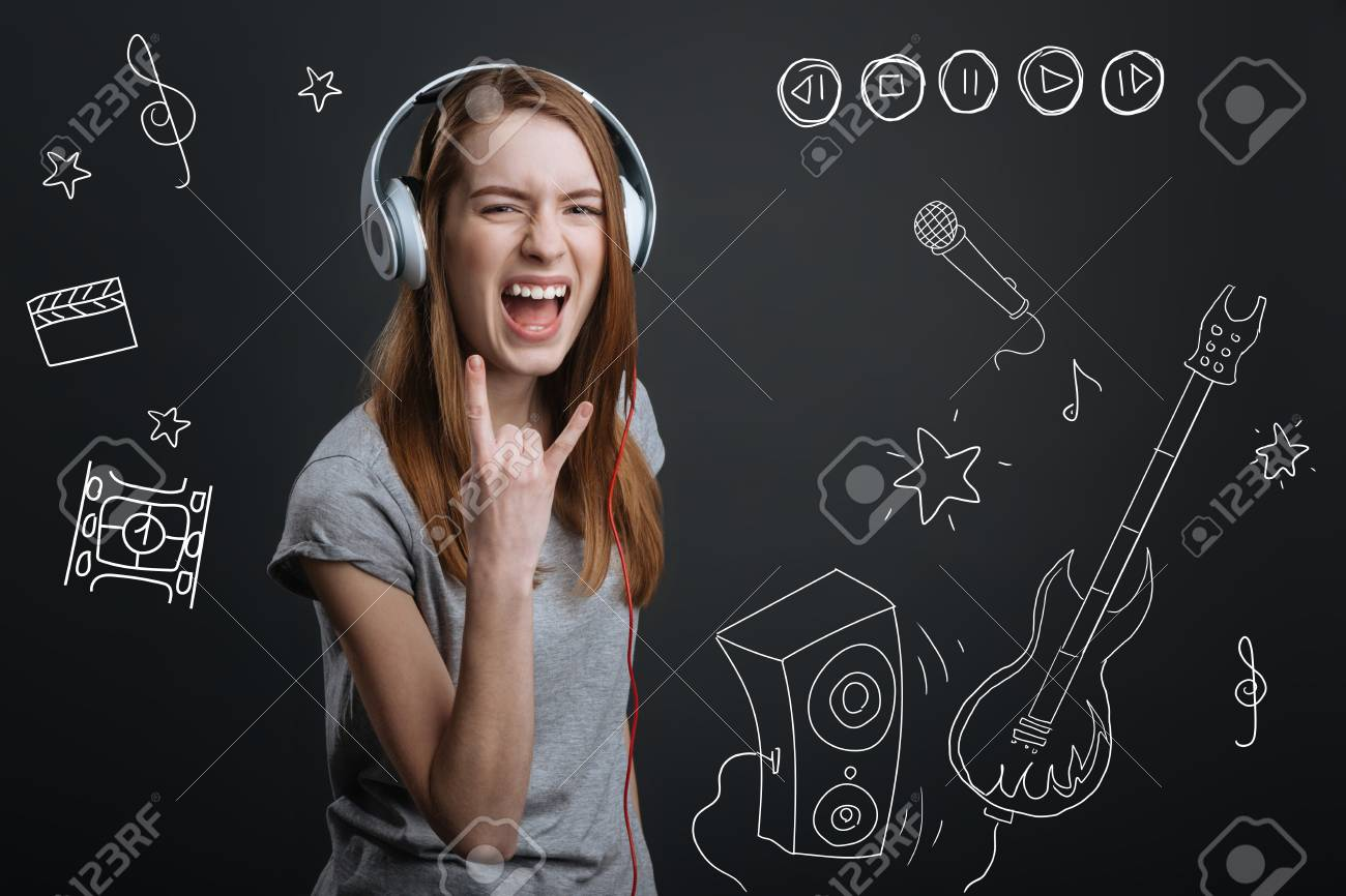Music lover  Emotional young positive music lover showing her