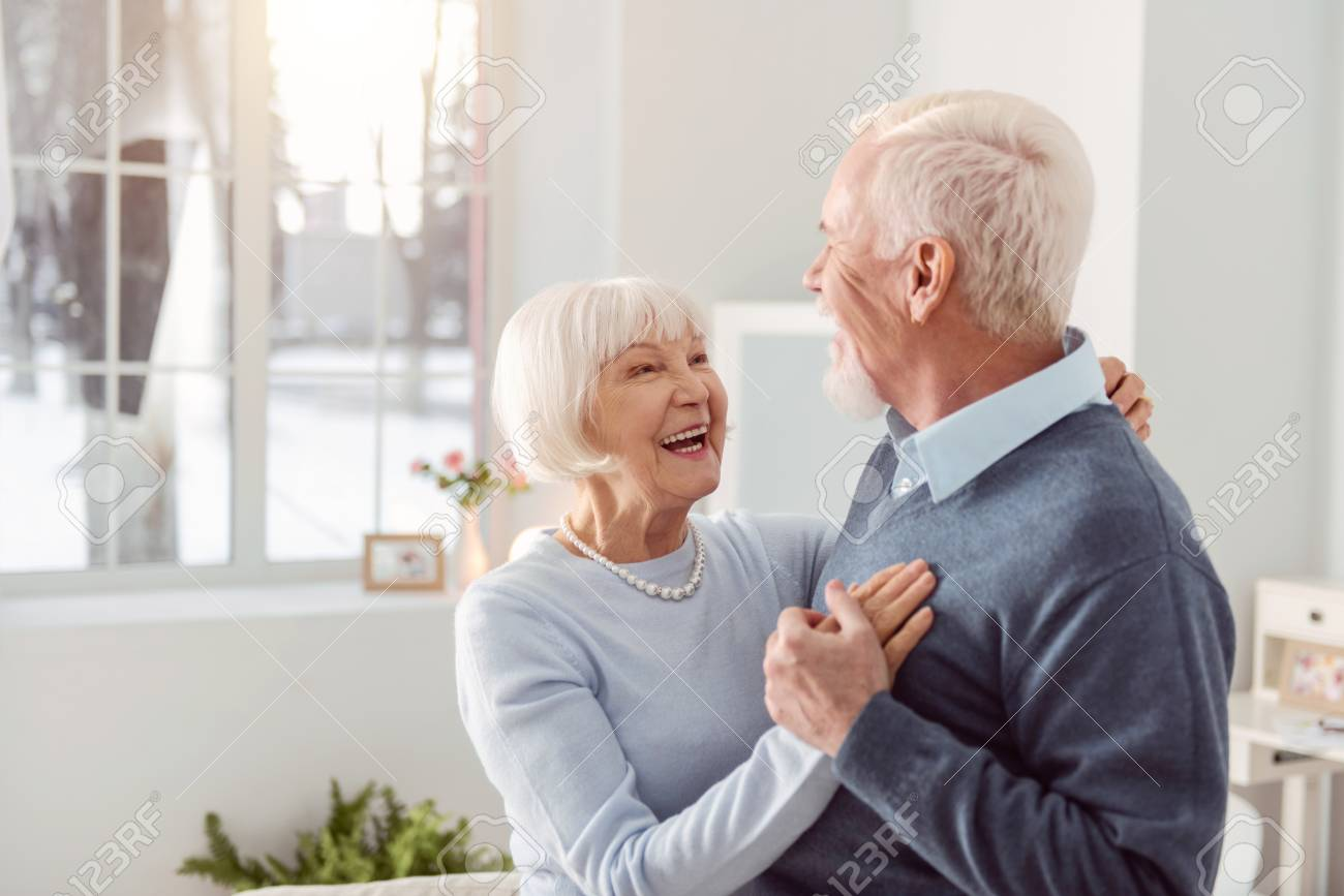 Loving couple. Joyful elderly husband and wife dancing in the living room while smiling at each other widely - 97923020