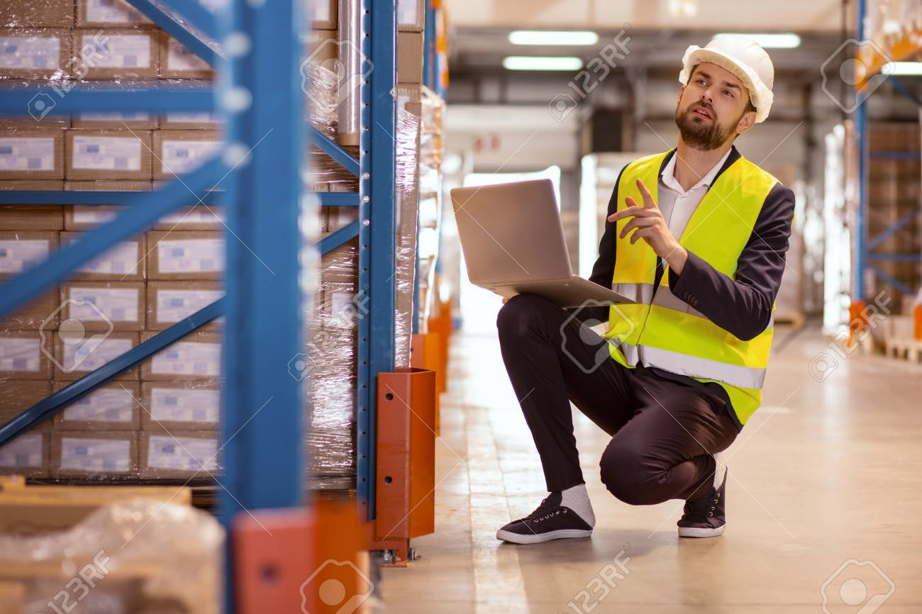 Inventory manager. Smart nice man holding a laptop and counting boxes in the warehouse - 100264904