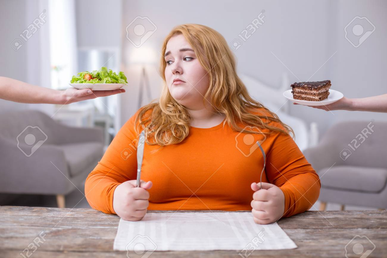 Being fat. Miserable plump woman looking at a salad and wanting cookies - 101052960