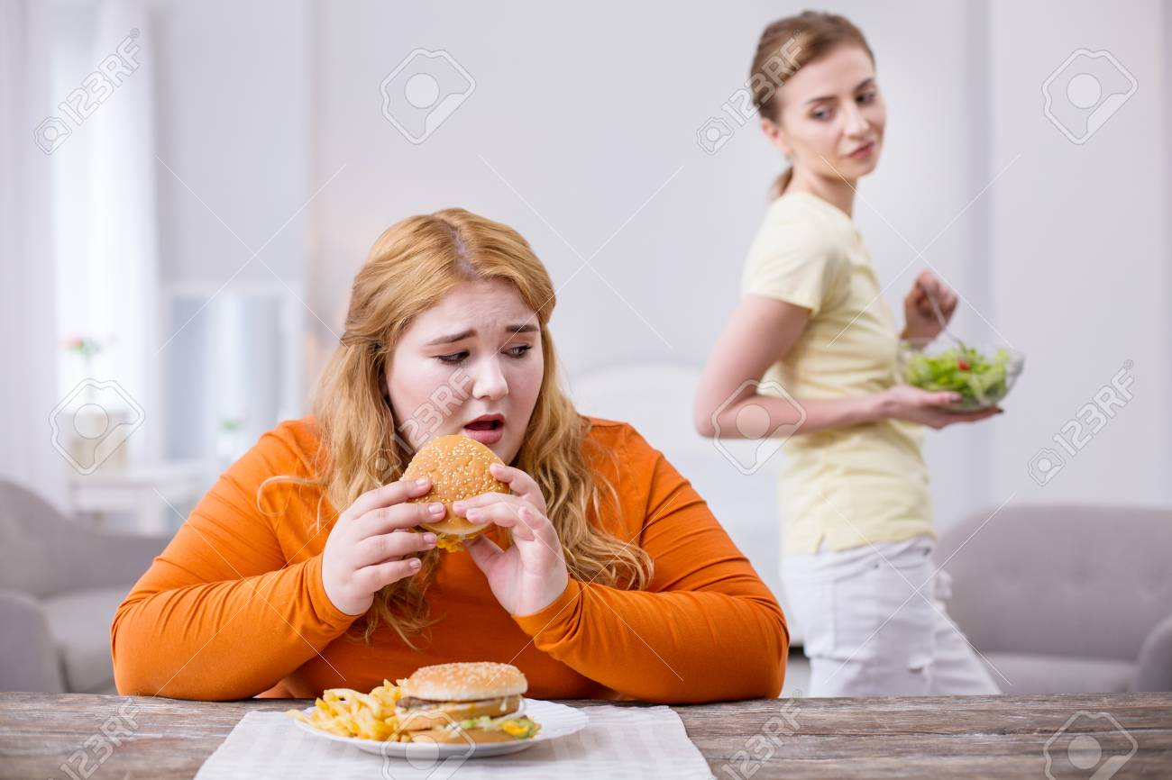 Being an outcast. Miserable stout woman eating a sandwich and her slim friend smirking - 101053155