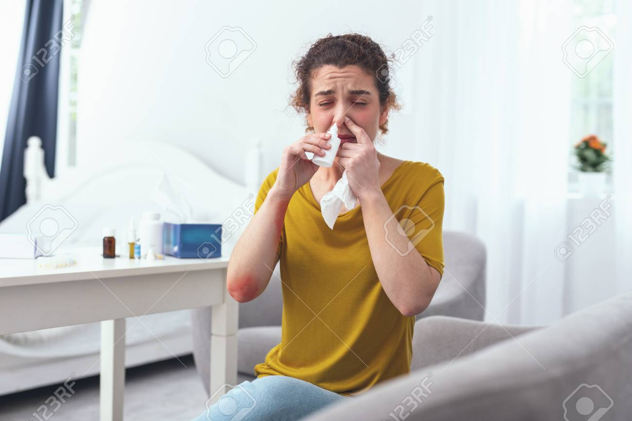 Cure for nose. Young curly woman sitting on a grey couch by the white table while using nasal spray for her runny nose - 102002562