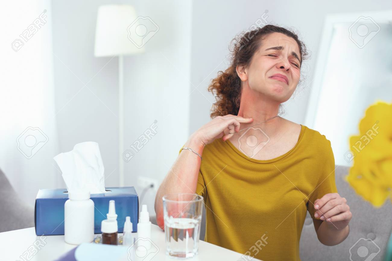 Metal intolerant. Young housewife wearing necklace feeling discomfort and pain discovering it causes her soreness and itchiness - 102002420