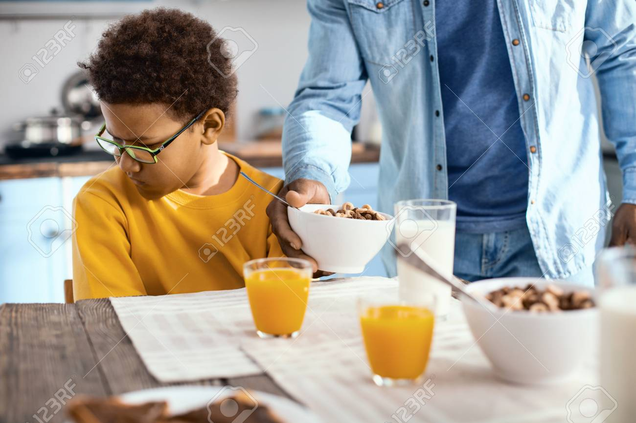 Not hungry. Cute pre-teen boy turning his face away from his father giving him a bowl of cereals, expressing his reluctance to eat - 102002619