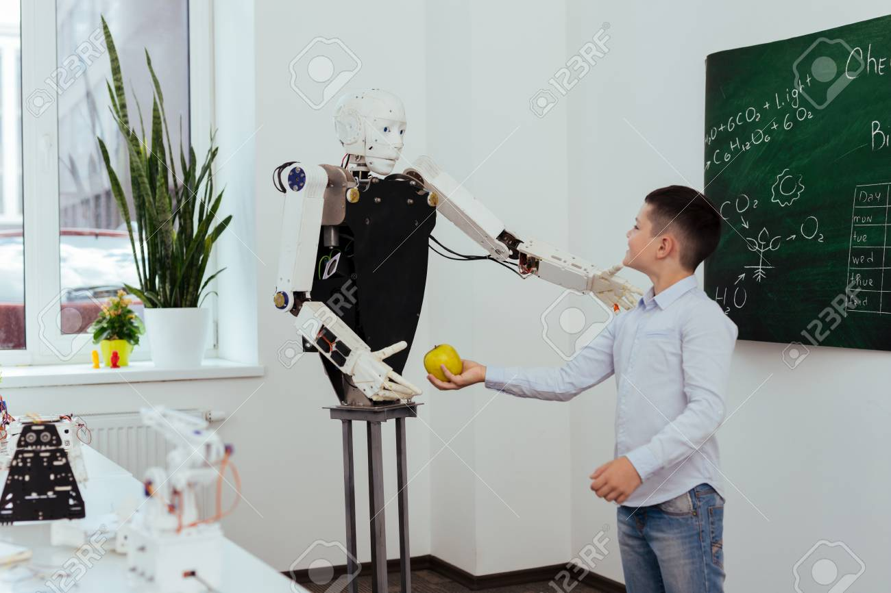 Take it. Happy cute boy holding an apple while giving it to the robot - 104576839