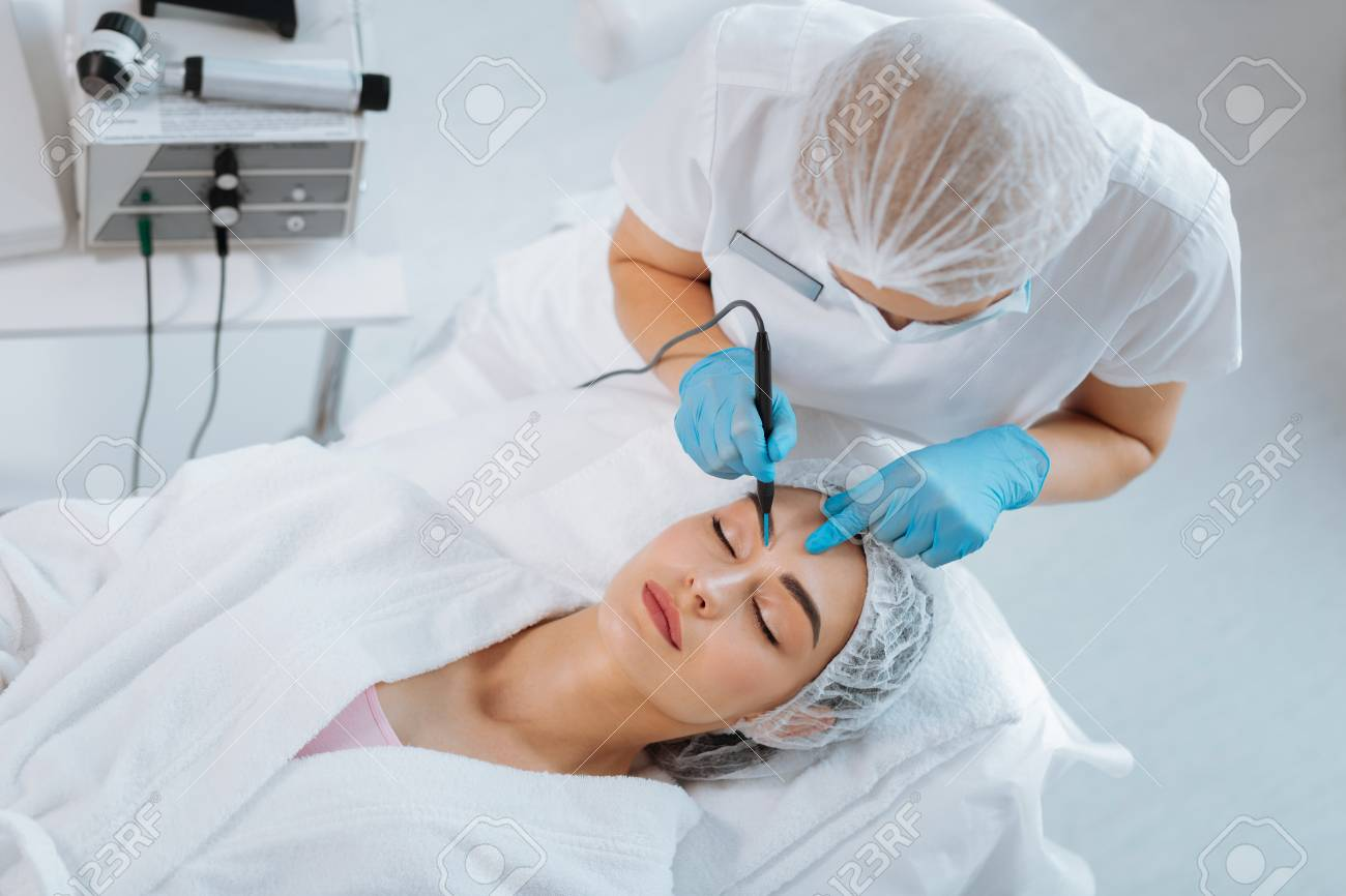 Professional cosmetology. Smart skilled cosmetologist removing a mole while working in the clinic - 107104243