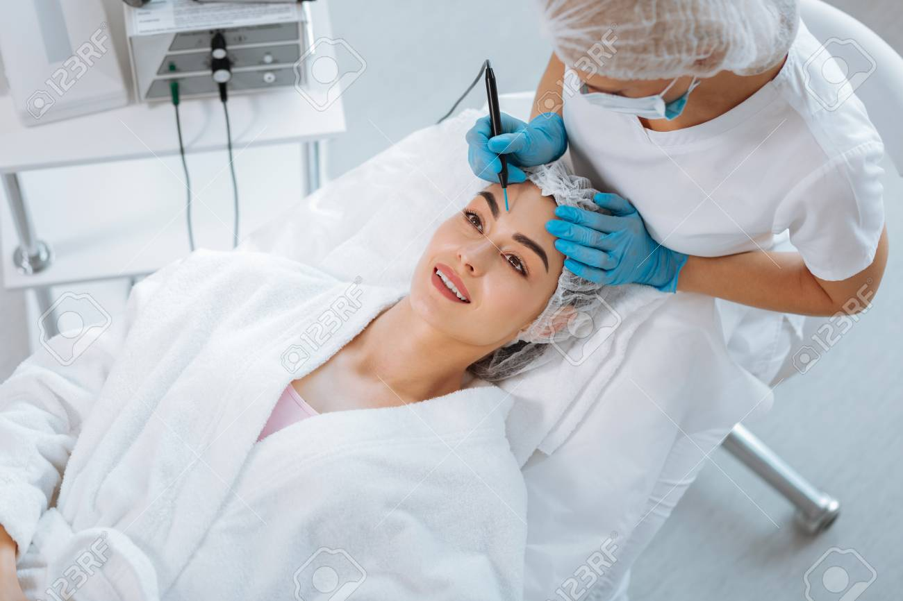 Aesthetic look. Delighted positive woman smiling while feeling happy about the cosmetology procedure - 107104245