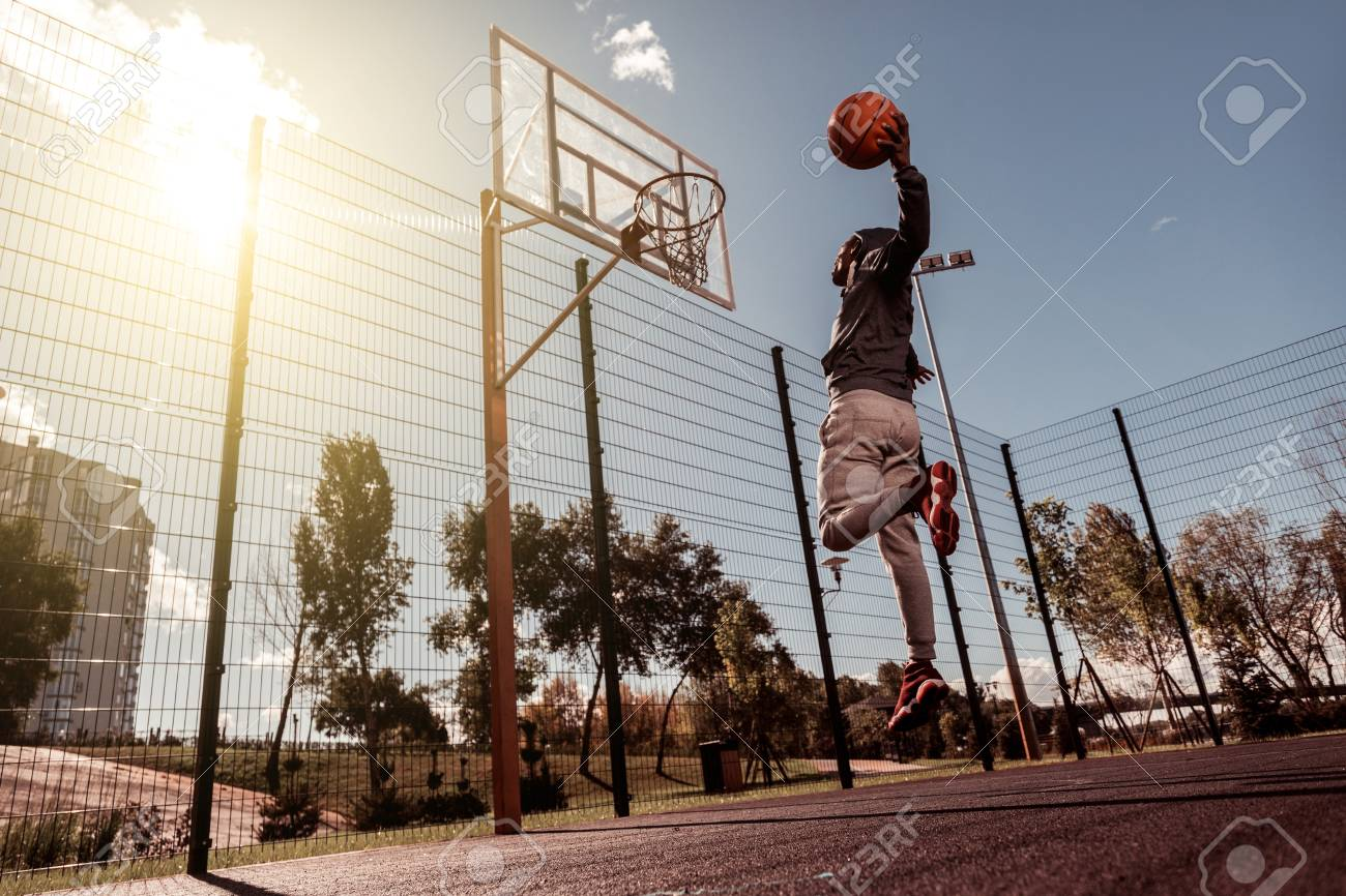 Perfect hit. Handsome Afro American man holding a ball while throwing it into the basket - 111302794