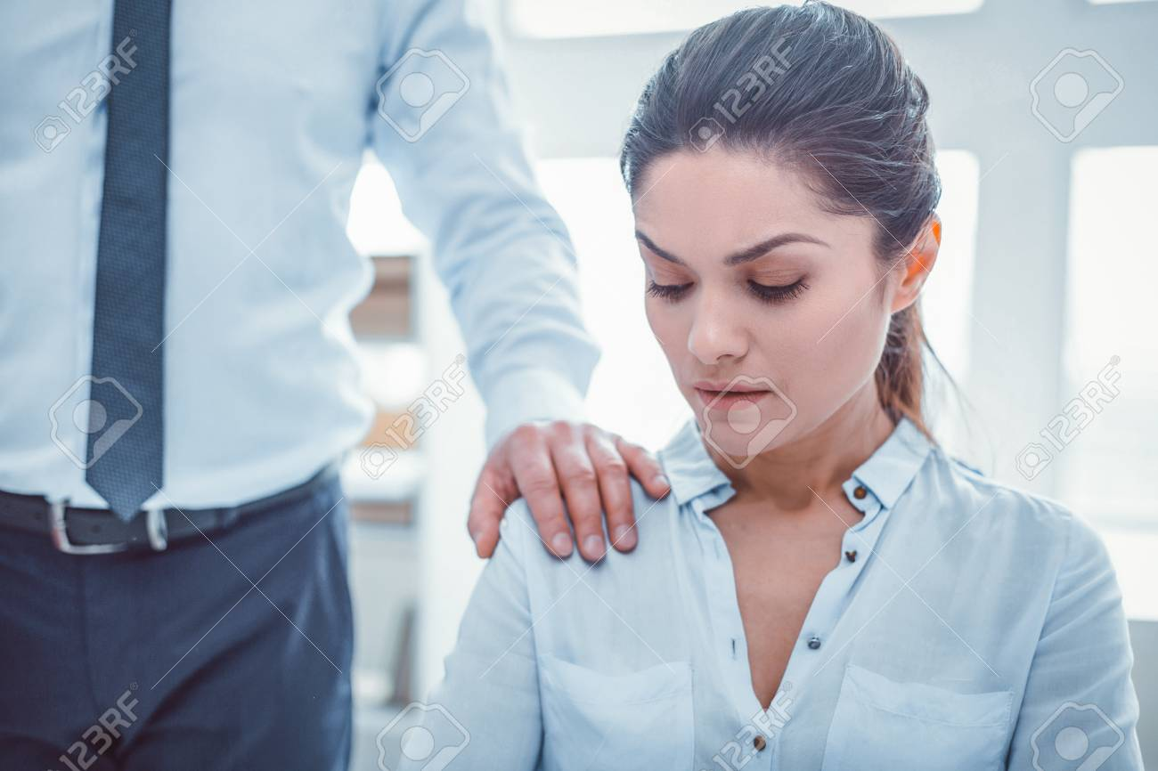 Boss touching secretary. Man in official clothes putting his hand on woman shoulder without permission - 112555129