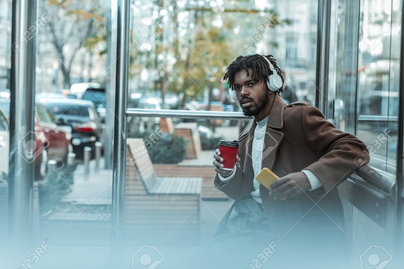 So concentrated. Serious bearded man wearing headphones and drinking coffee - 116022903