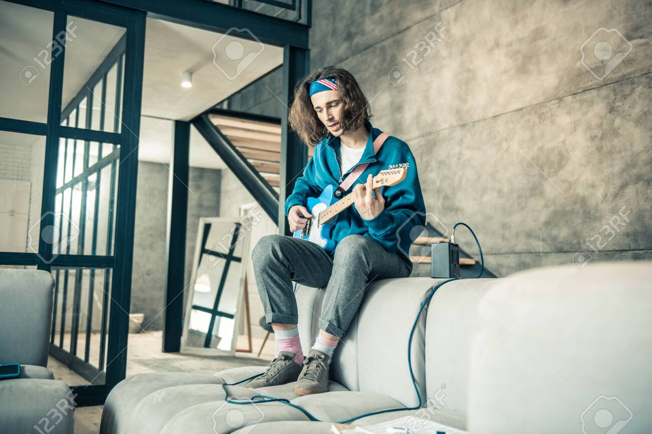 Connected to amplifier. Stylish talented young guy wearing bandana on long hair while creating new song - 120179585