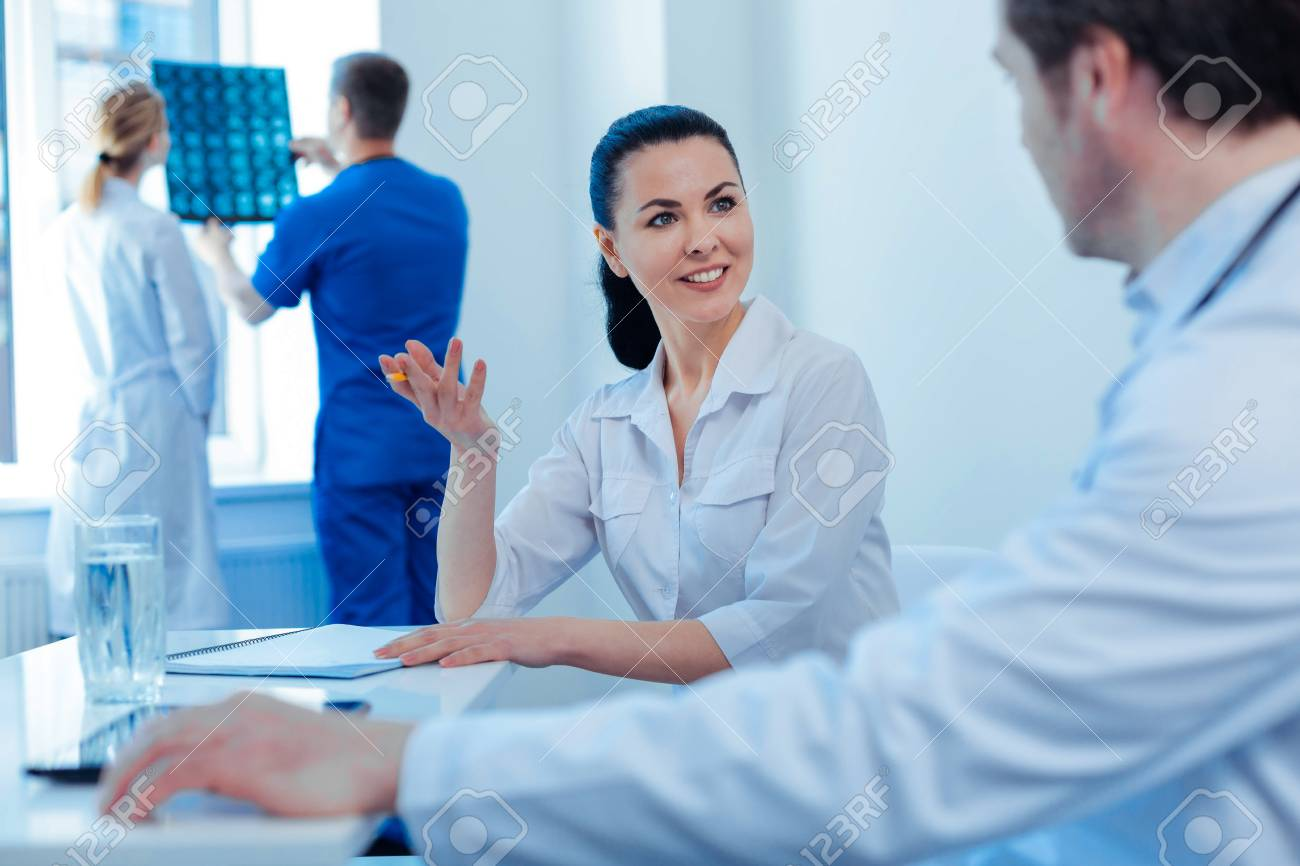 I am in all ears. Delighted medical worker keeping smile on her face and actively gesticulating while consulting her coworker - 120186405