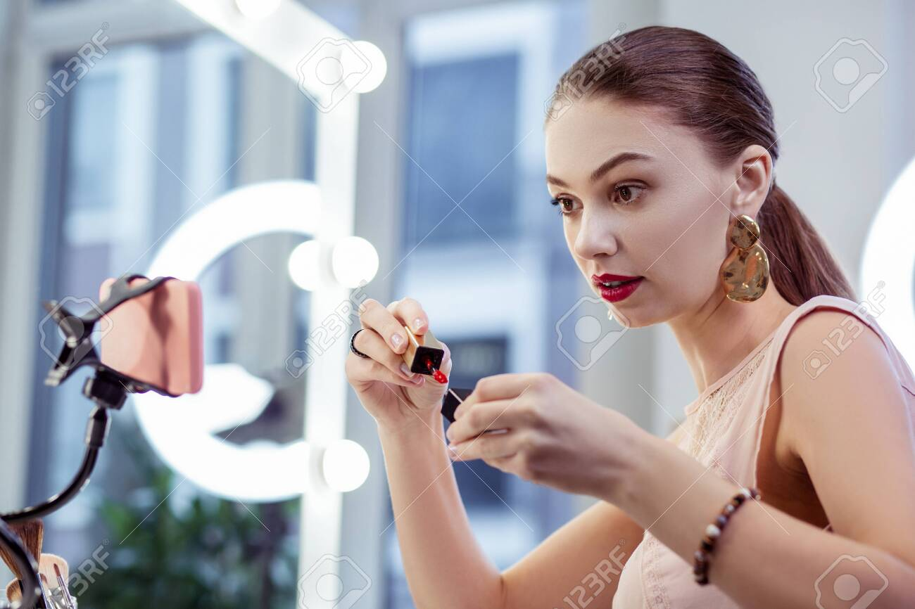 Bright colour. Nice happy woman showing a shiny lipstick while recording a video for her blog - 122254816