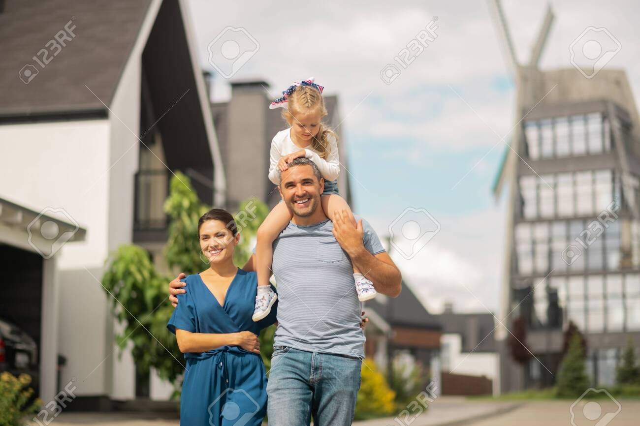 Having family walk. Lovely cute daughter sitting on neck of father while having family walk - 128660729