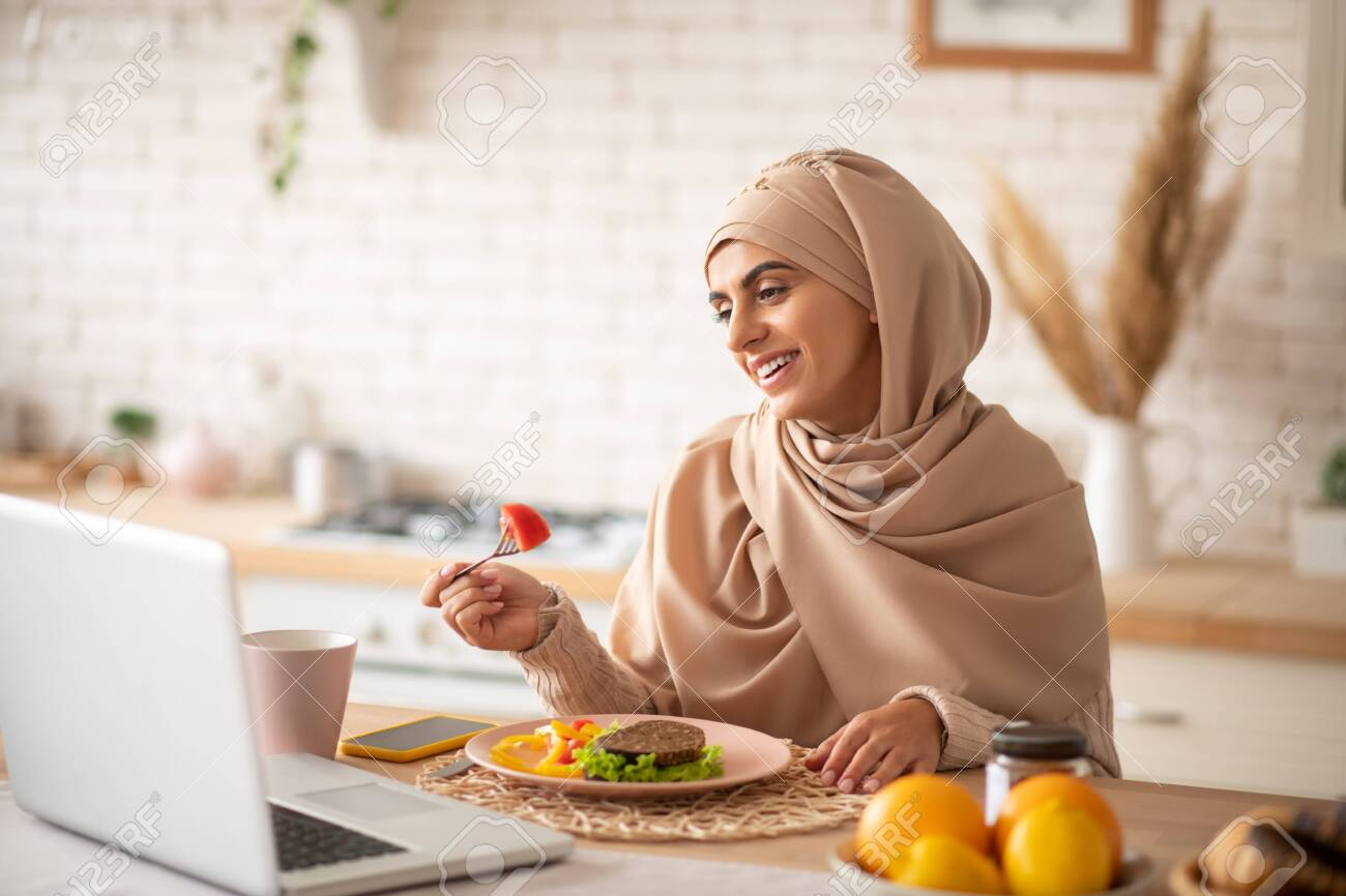 Balanced dinner. Muslim girl enjoying a healthy balanced dinner while watching funny videos on her laptop - 132543762