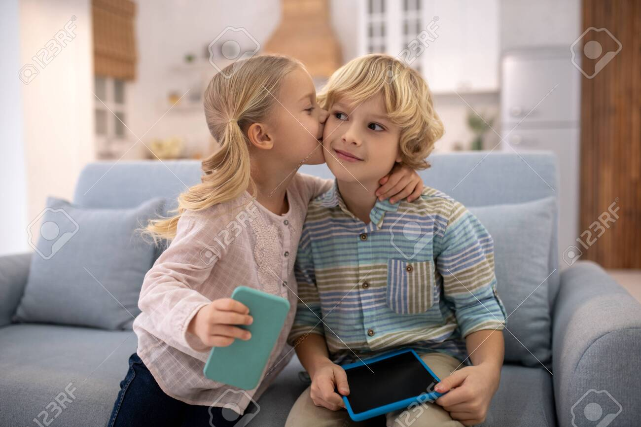 At home. Children sitting on sofa, holding gadgets, girl kissing and embracing boy, both are happy - 139911451
