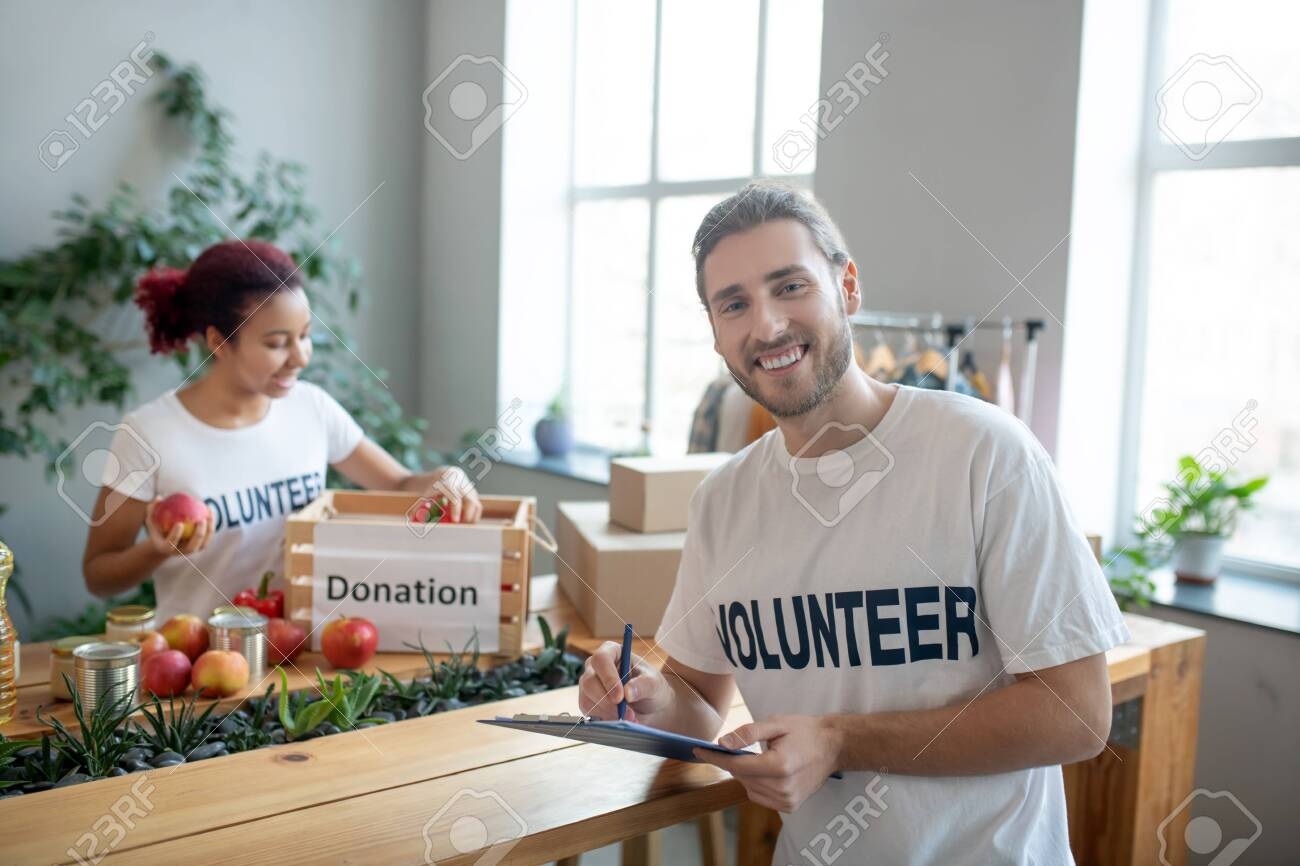 Food aid. Young man in front of the table writing notes, the girl at the table putting apples in a charity box, both of them in a good mood. - 140078164