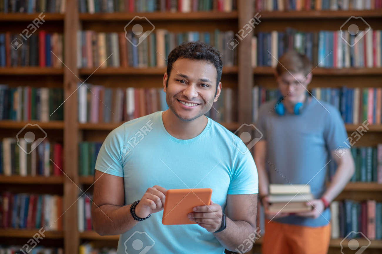 Gadget. Dark-haired young latino in a blue tshirt holding a tablet - 142900960