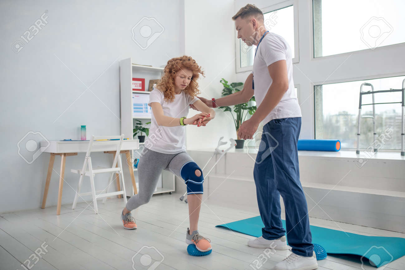 At rehabilitation center. Male physiotherapist helping female patient with lunging - 143834672