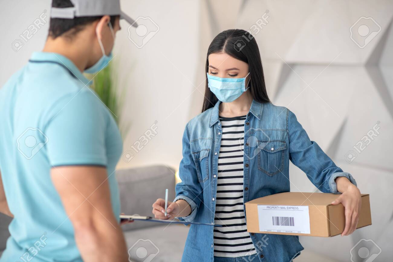 Receipt of parcel, signature. Dark-haired young woman with a parcel signing a document held out by a man in a cap, both wearing protective masks. - 146161407