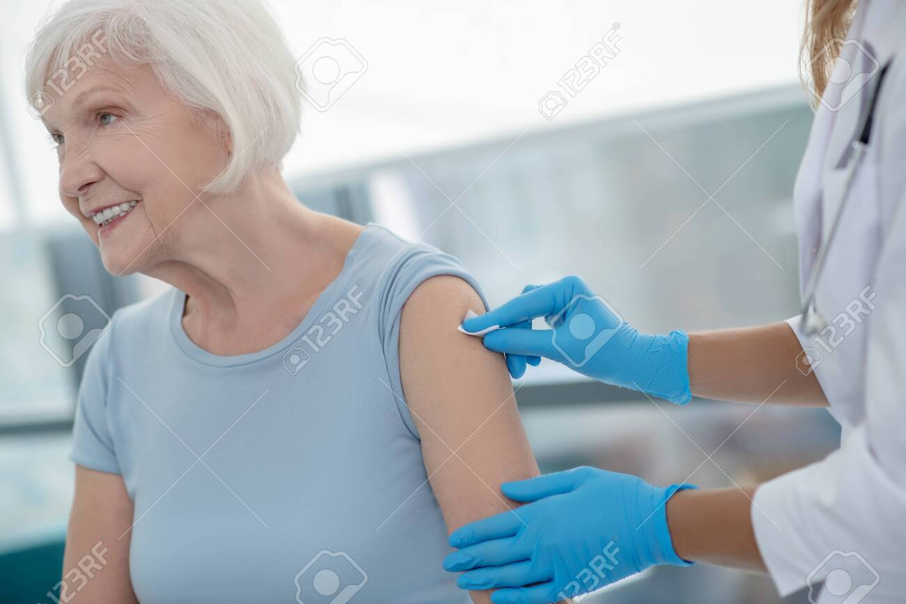 Injection. Nurse making an injection to an elderly smiling woman - 157939589