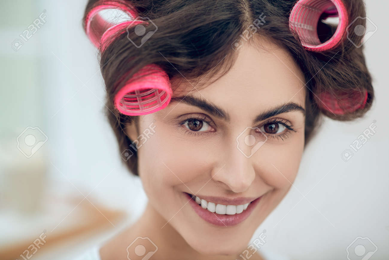 Close-up face of beautiful young woman in hair curlers - 166230352
