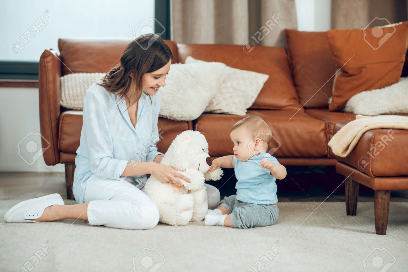 Mom showing teddy bear to interested child - 167898901