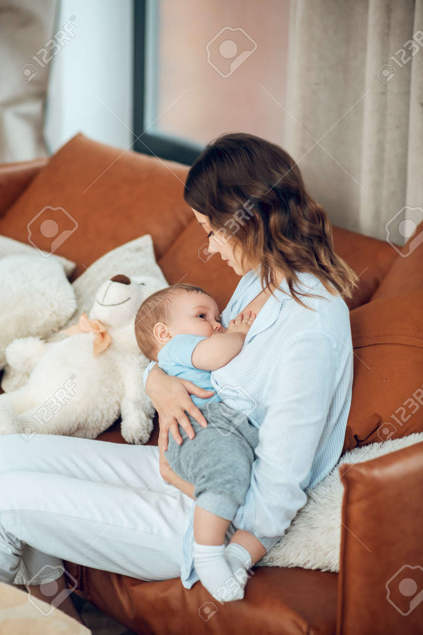 Mom feeding her baby sitting on couch - 167898906