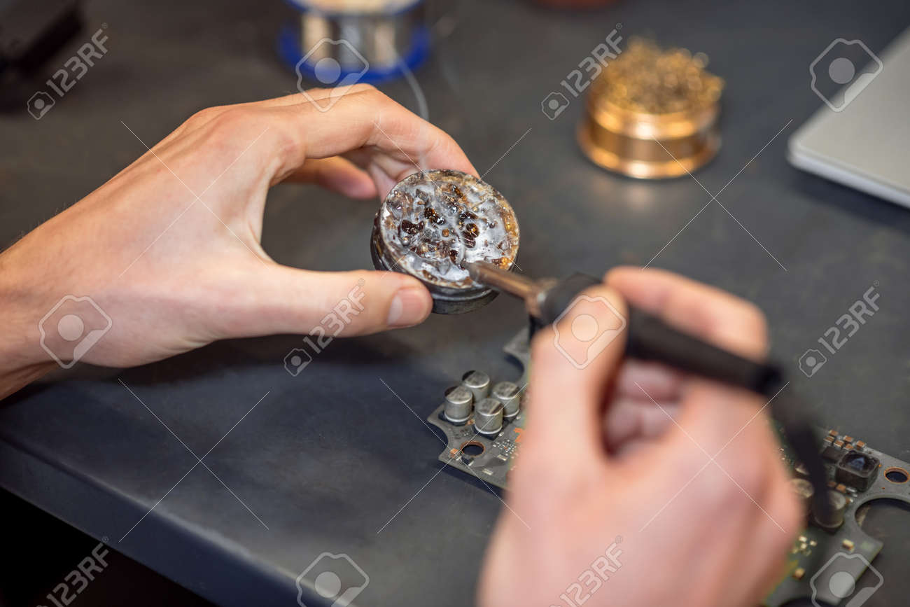 Hands with hot soldering iron touching solder - 167899943
