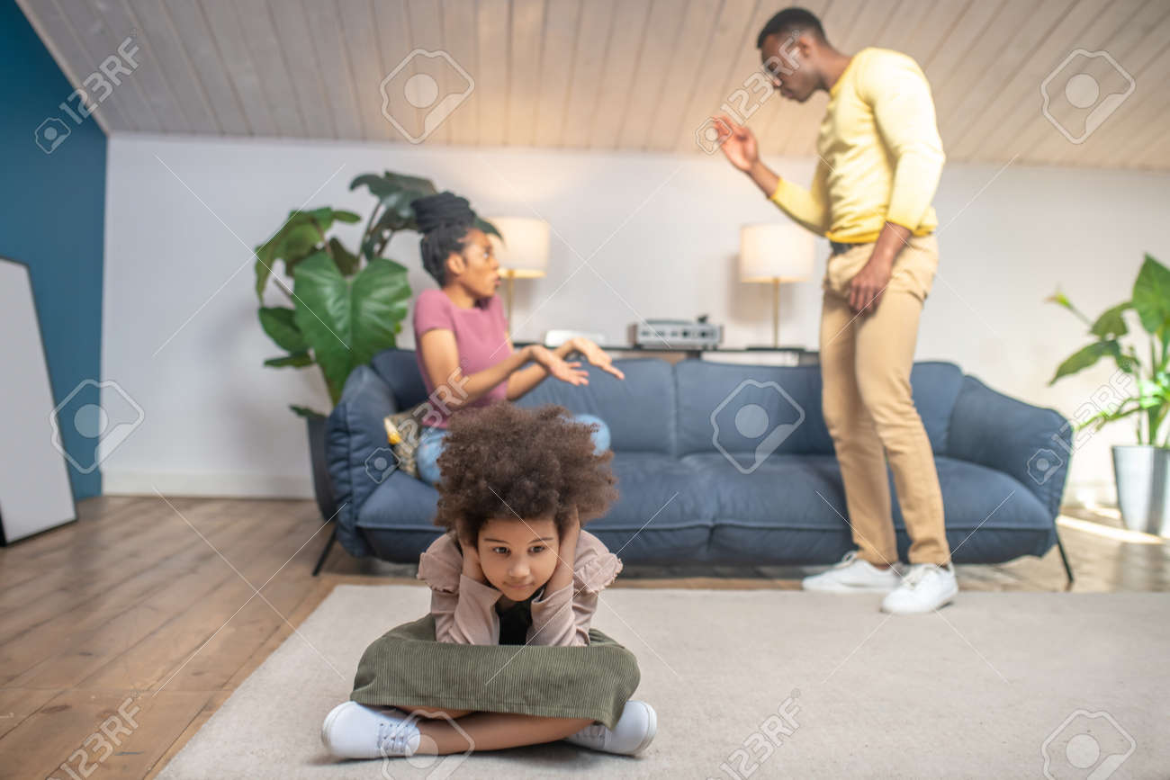 Parents swearing nervously and unhappy little daughter - 171576601