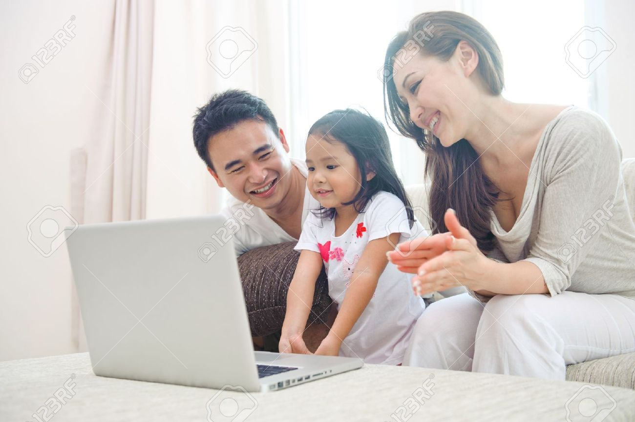 Happy Asian Family using laptop with daugther Stock Photo - 11187589