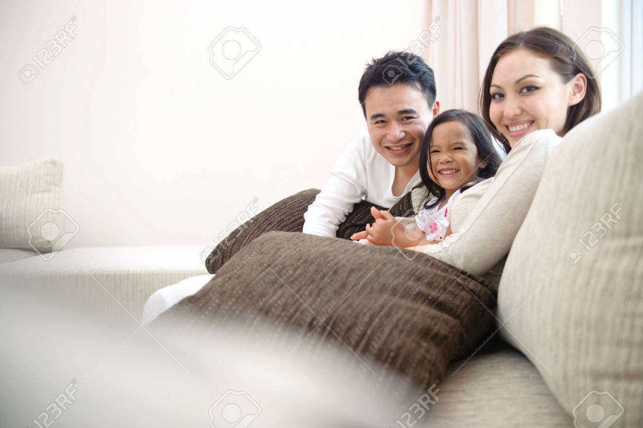 Family Smiling Happily In The Living Room Stock Photo, Picture And ...