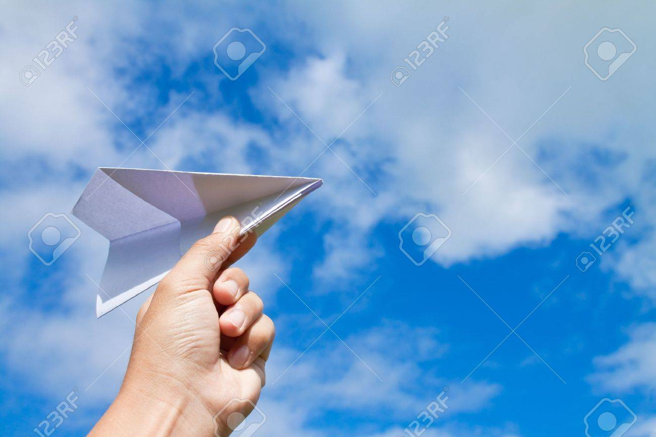 hand with paper plane against blue sky Stock Photo - 9492790