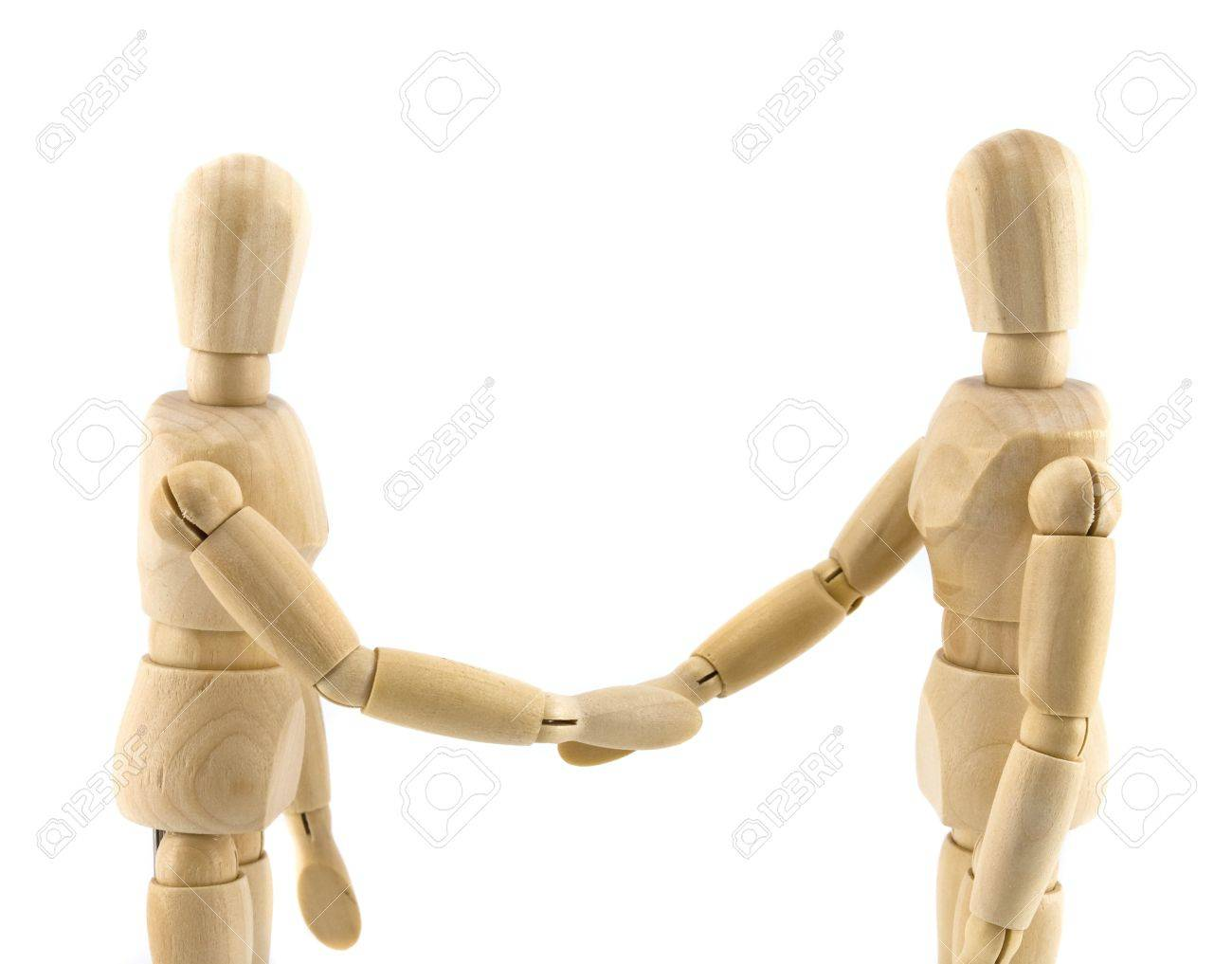 Wooden dummies shaking hands, Cooperation of business Stock Photo - 10571399