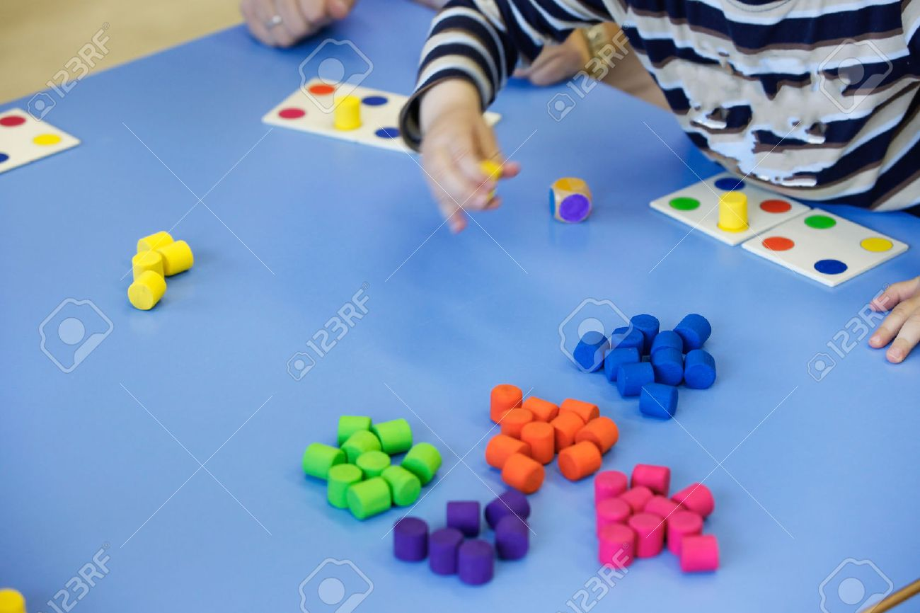 Children playing with homemade, do-it-yourself educational toys, arranging and sorting colors. Learning through experience concept, intelligence development, educational approach concept. - 57972727