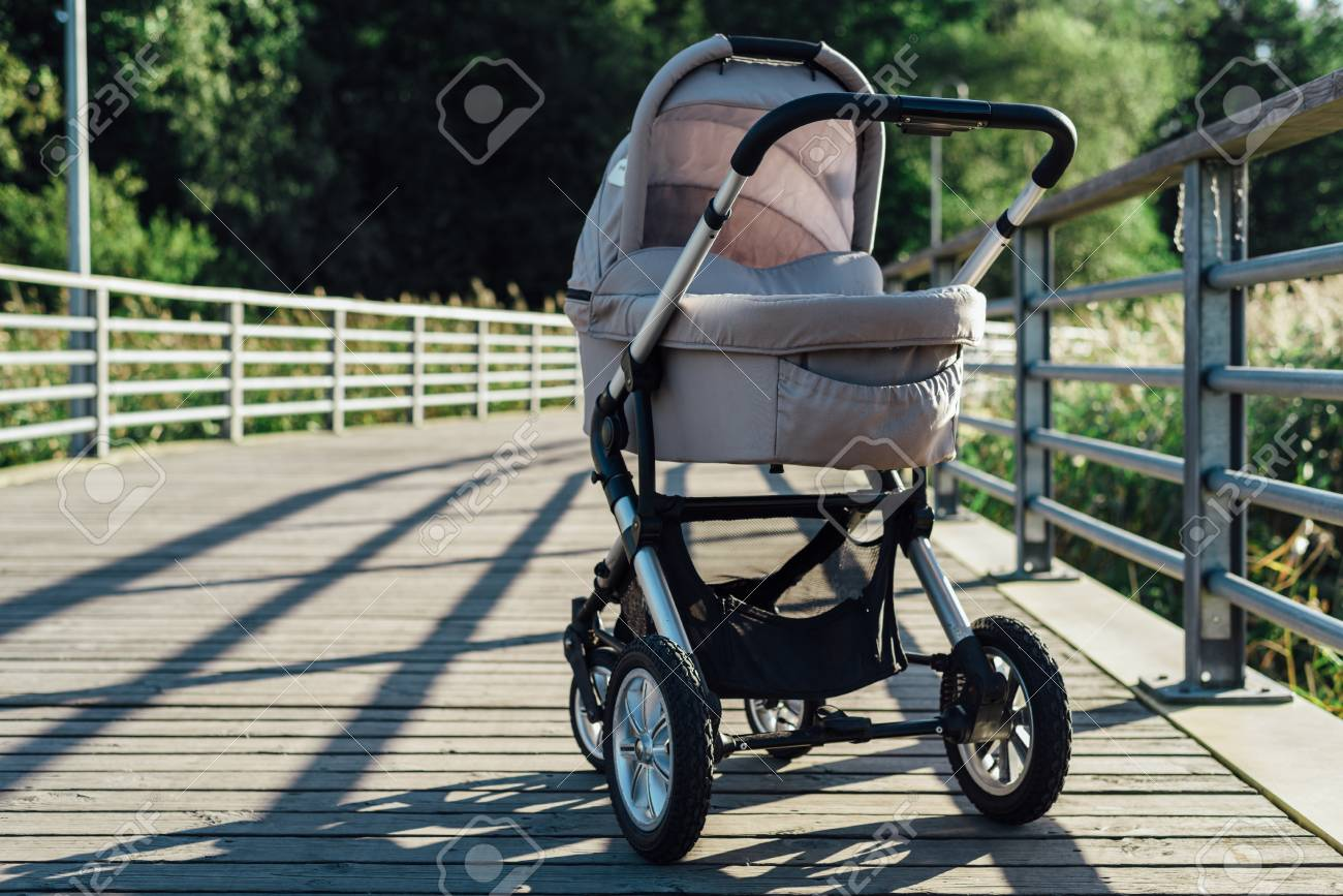 62891406 baby stroller on running path in park at sunny day