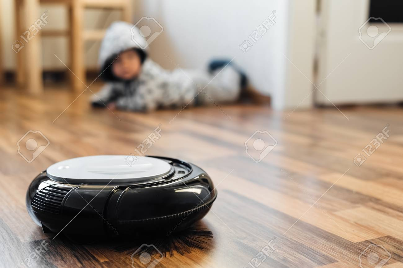 Robotic Vacuum Cleaner On Laminate Floor With Baby Boy Background Stock Photo 66718121