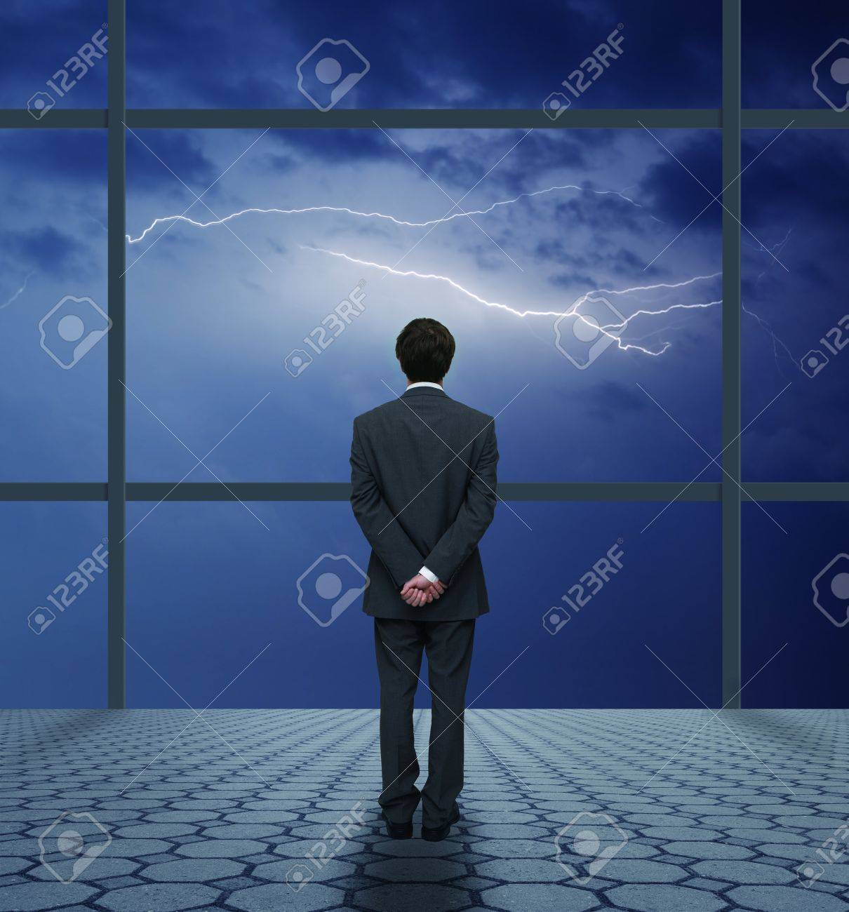 Businessman looking out the window at the storm Stock Photo - 20112769