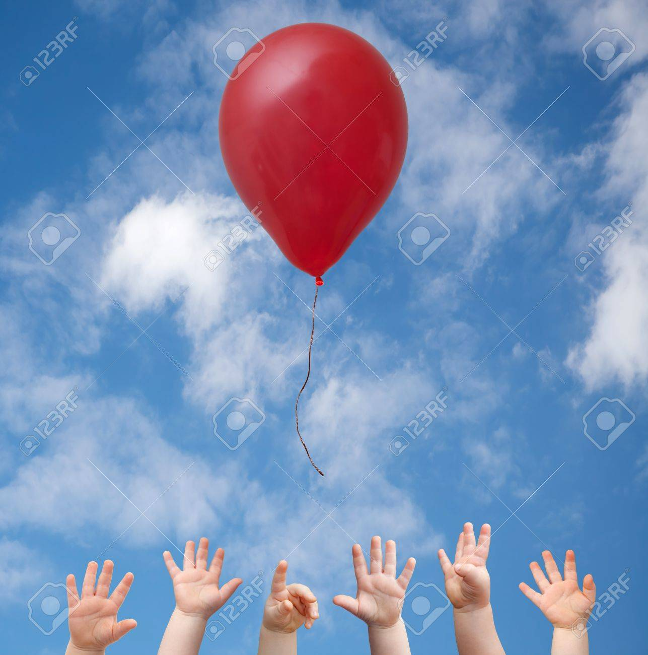 Hands of young children reaching for red balloon Stock Photo - 20142950