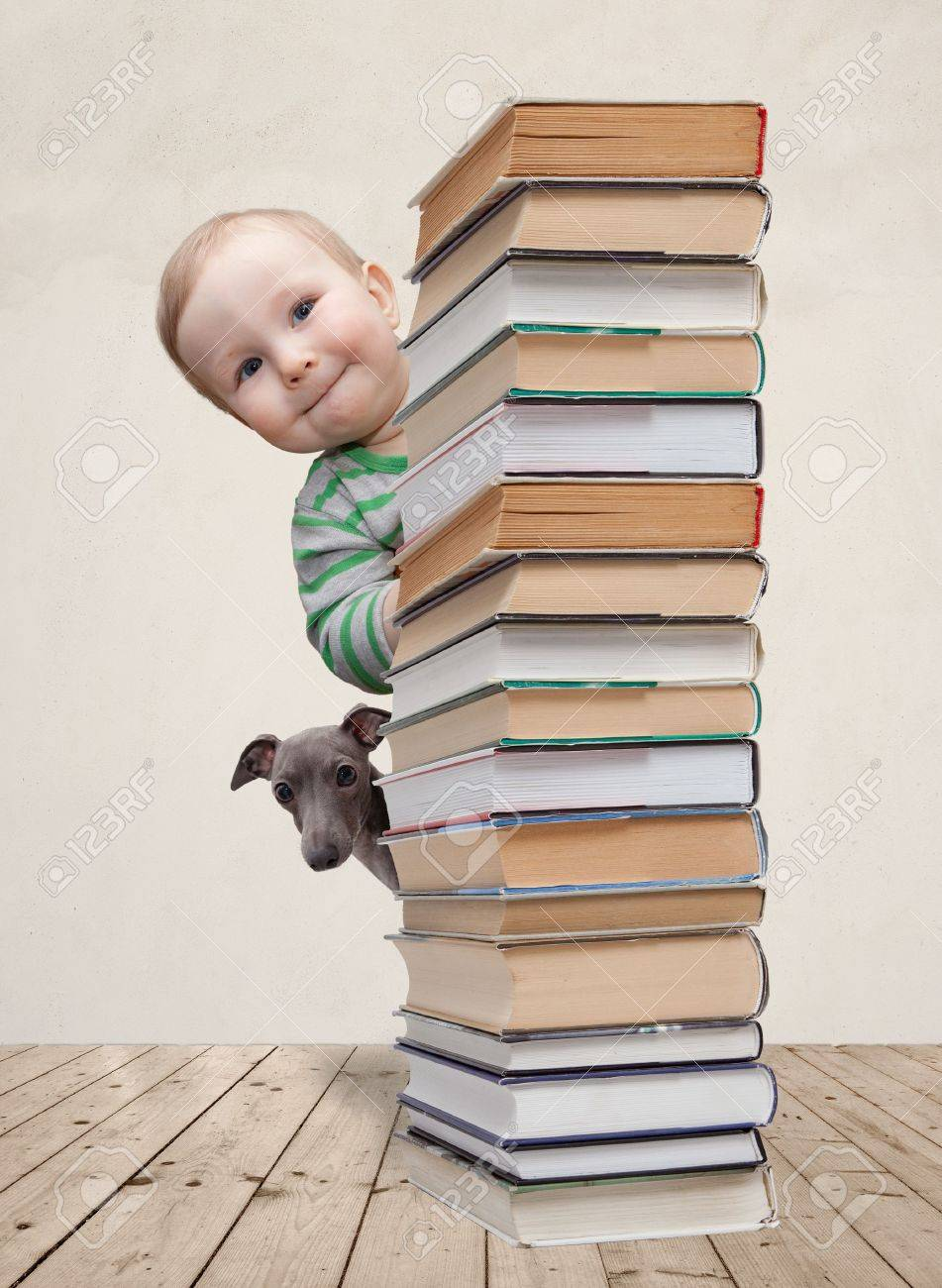 Baby and dog looking behind the column of books stock photo 20960845