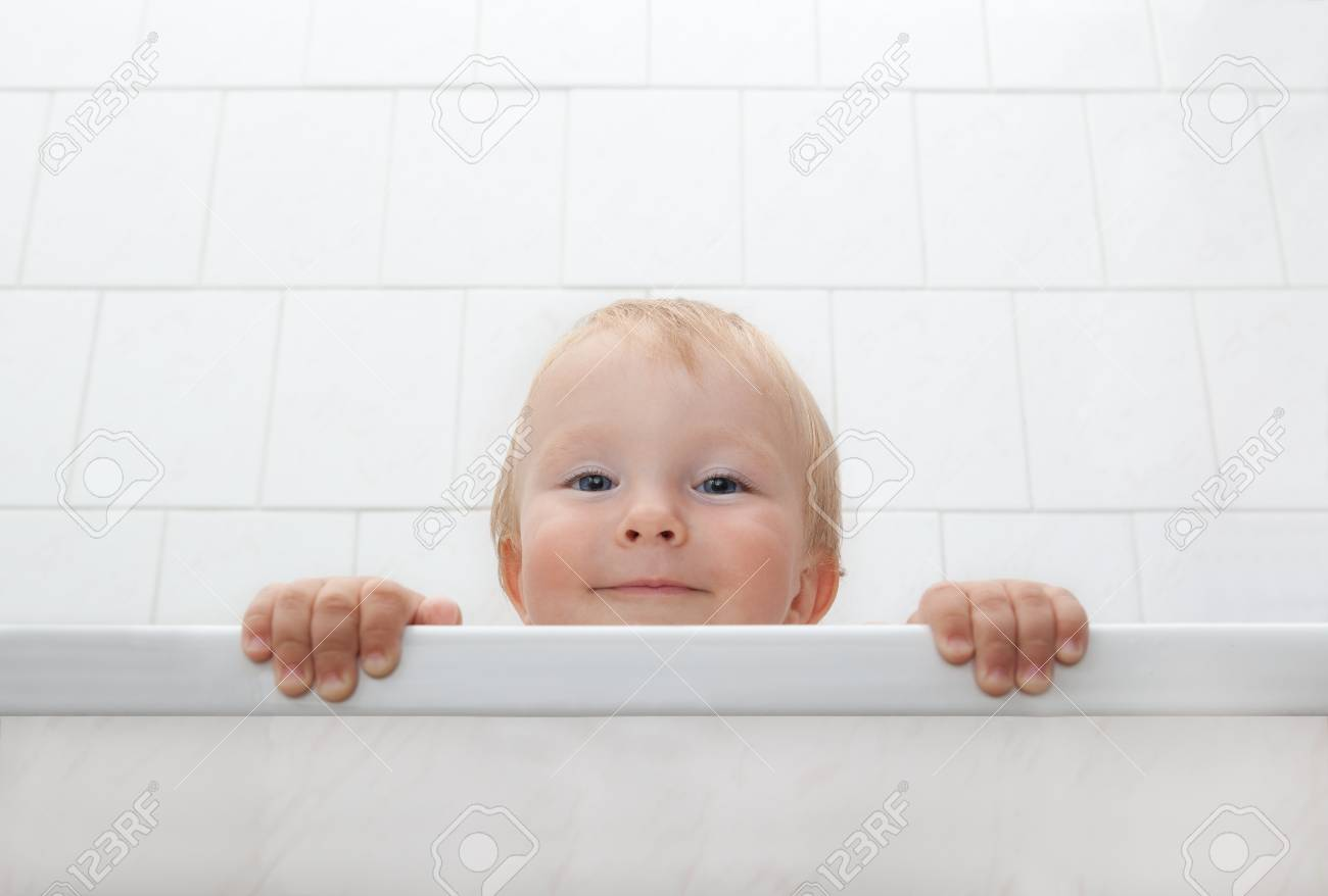 Picture of a little boy looking out of bathtubs Stock Photo - 21379760