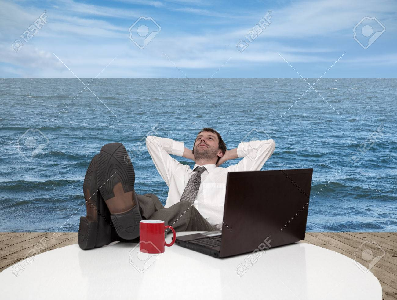 Young businessman relaxes on a pier by the sea Stock Photo - 29223016