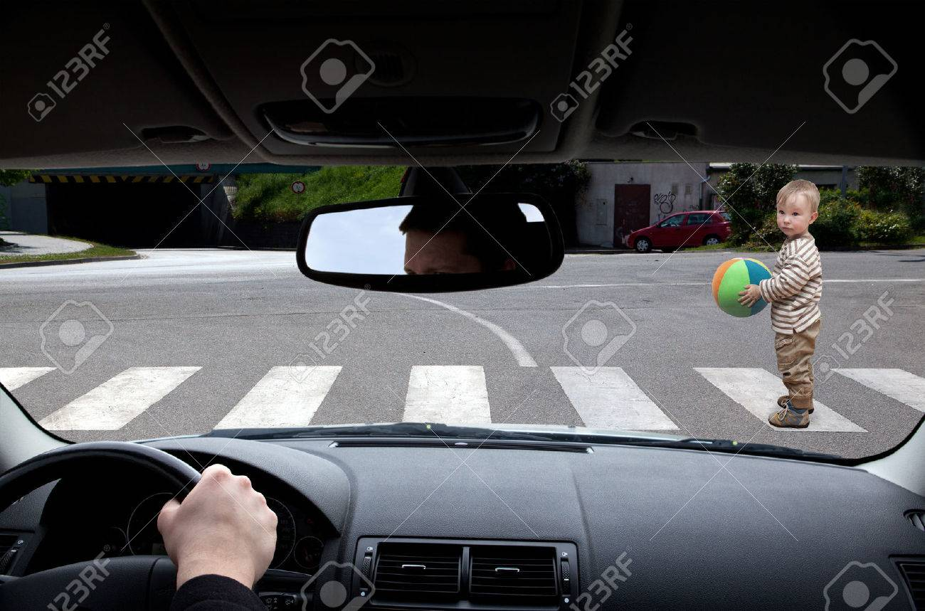 baby with ball tries to cross the road Stock Photo - 58597418