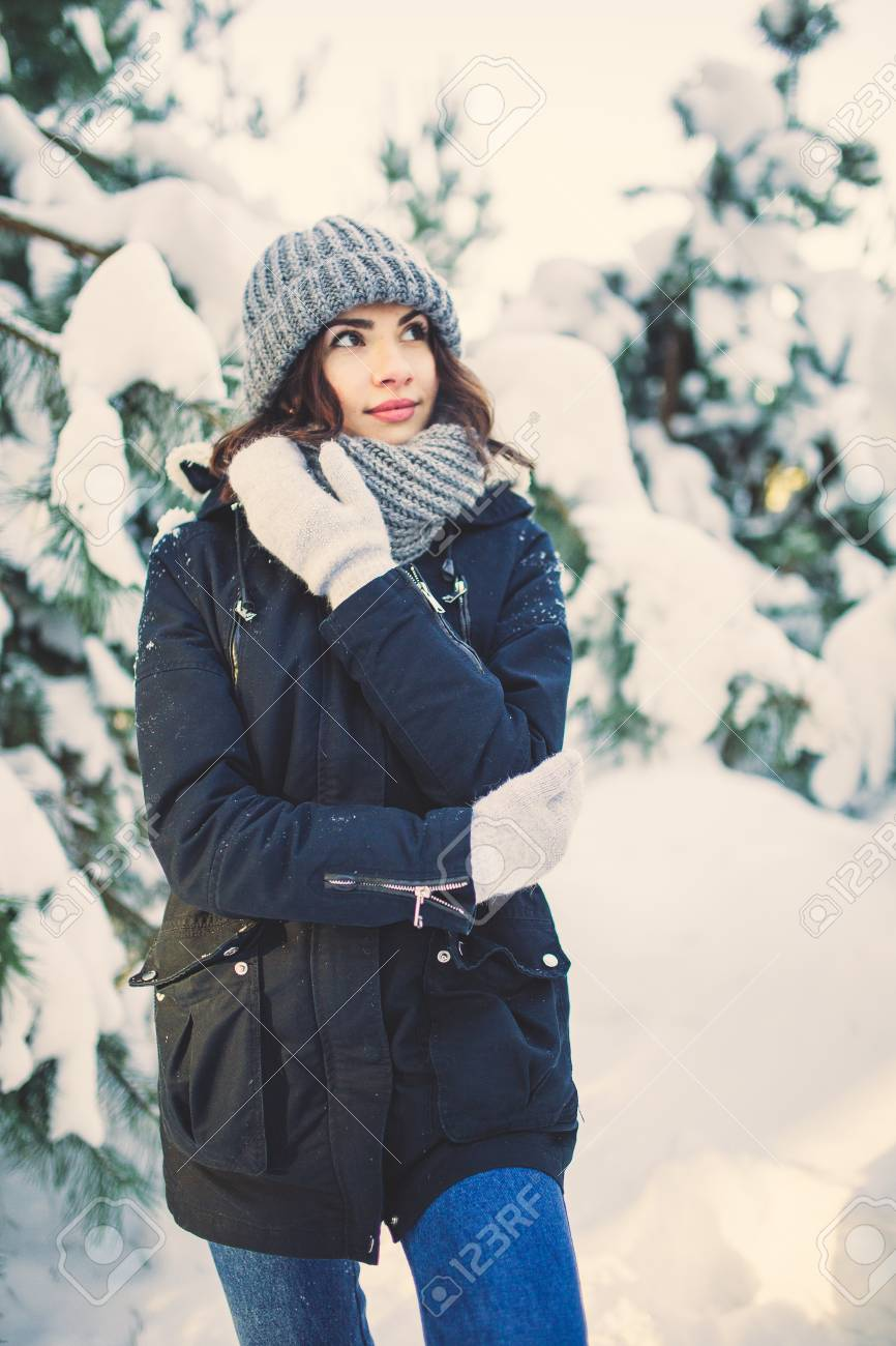 b28a78cbabf95d Beautiful young woman in winter jacket, knitted beanie hat and scarf,  outdoors in the