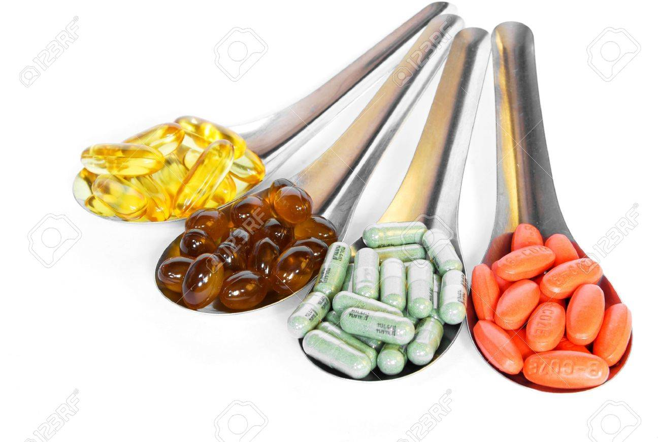 spoon with colorful vitamin medicine pills on white background Stock Photo - 9155027