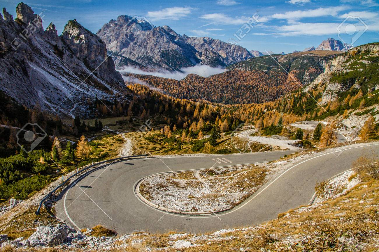 Winding road within Colorful Autumn Forest, Cloudy Blue Sky and Mountains-Dolomites,Italy - 38375726