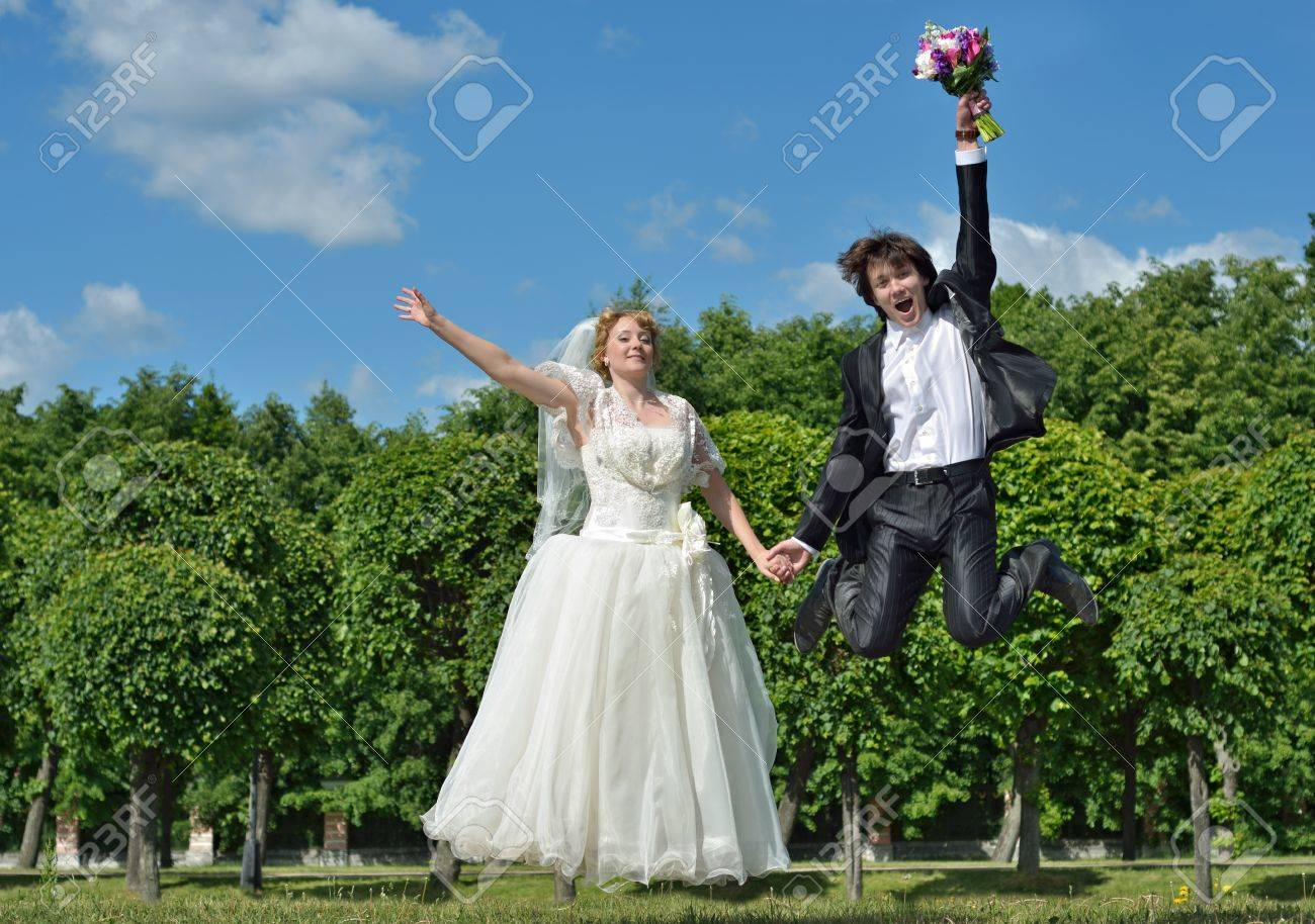 A just married couple, very happy groom and blonde bride jump high on their wedding day Stock Photo - 13667497